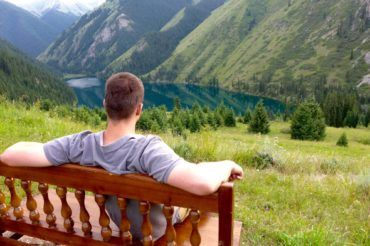 Tourist looking from the bench at Kolsay Lake kazakhstan travel
