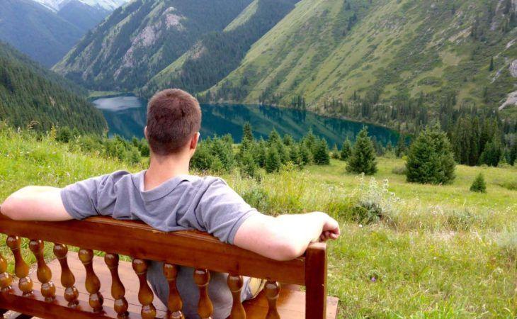 Tourist looking from the bench at Kolsay Lake kazakhstan travel