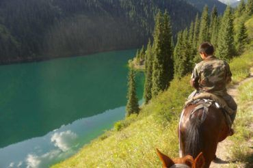 Horse riding along the second Kolsay Lake in kazakhstan's nature