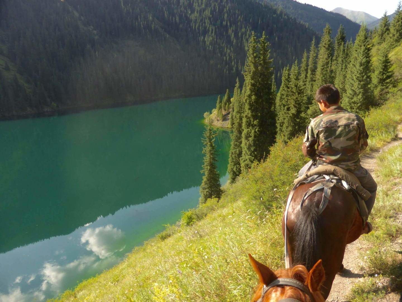 Horse riding along the second Kolsay Lake in kazakhstan's nature