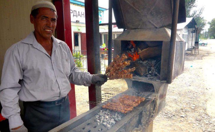 Men holding Shashlyk in front of local cafe in Kazakhstan food