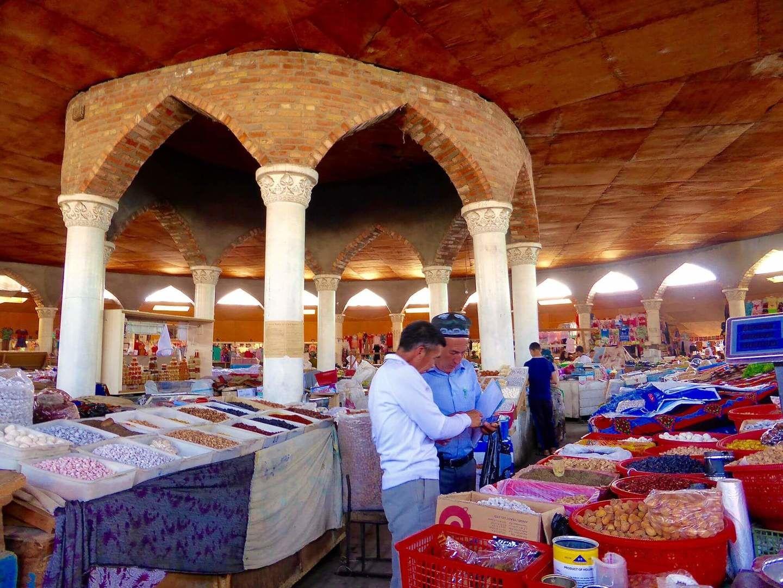 Penjikent Bazaar with two men looking at goods, Tajikistan