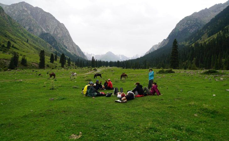 group resting in the mountains during hiking, kyrgyzstan, central asia tour