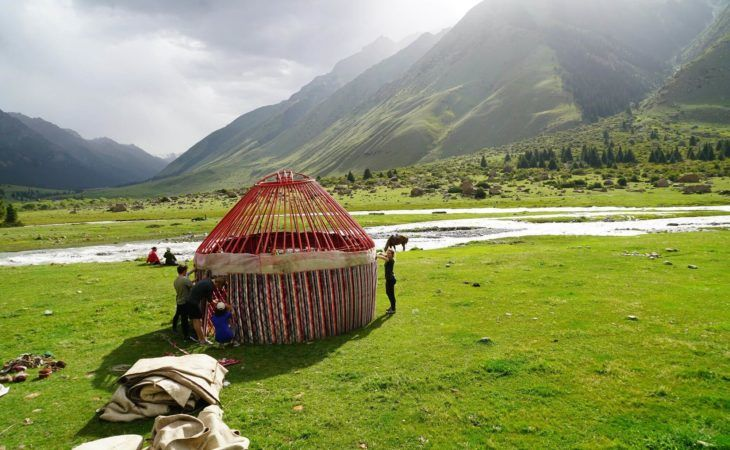 group of tourists builidng a yurt in the mountains of kyrgyzstan, central asia
