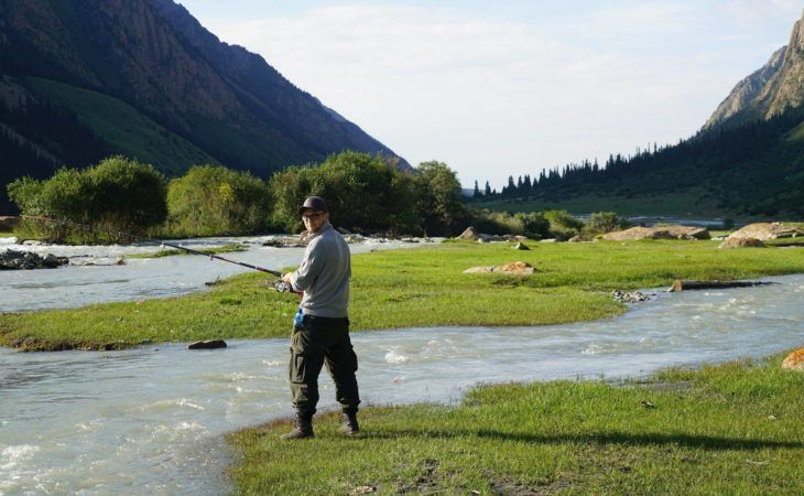 traveller trying to fish in the mountain river of kyrgyzstan