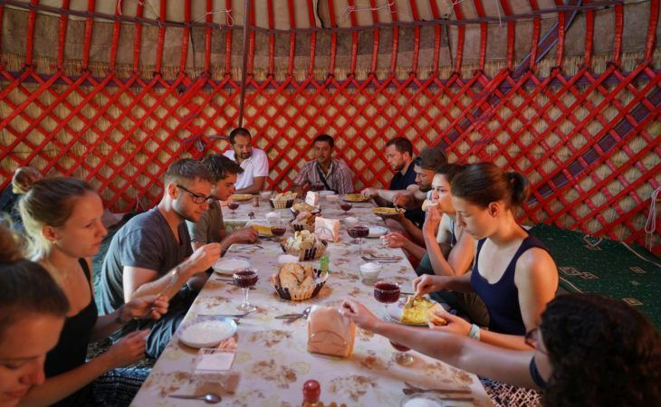 group of travellers eating local food in kyrgyzstan, central asia
