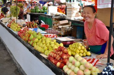 woman selling Fruits in Osh bazaar Kyrgyzstan travel people