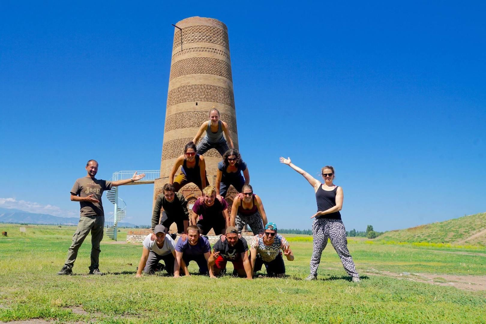 Group of travelers building human pyramid in front of Burana Tower in Kyrgyzstan Tours
