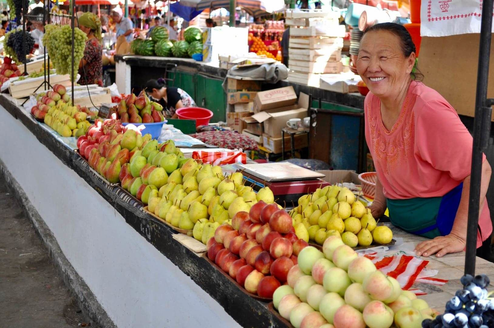 Fruits in bazaar sold by friendly lady, shopping in osh bazaar during Kyrgyzstan Tours