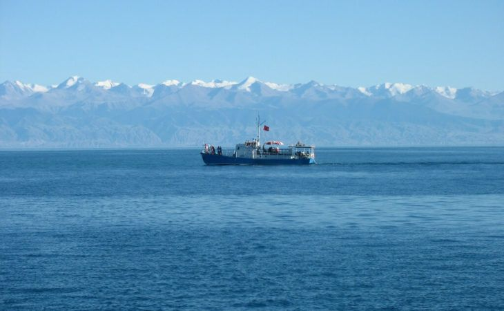 white boat in Issyk kul lake with tian shan mountains in the background