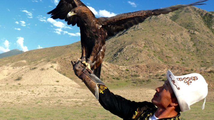 men in Kalpak with eagle in Kyrgyzstan