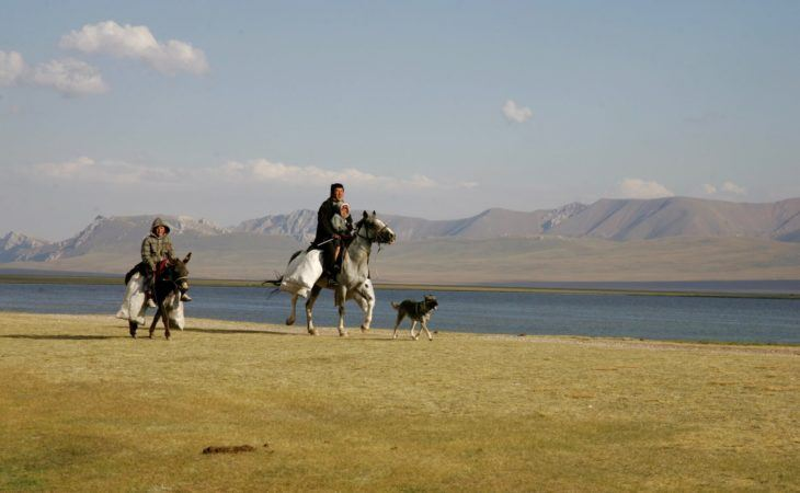 Kyrgyzstan people in Song Kul travel home through beautiful landscape on horse and donkey