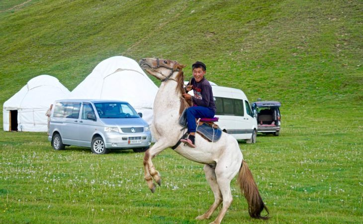 local boy on horse in kyrgyzstan mountains, in front of the yurt