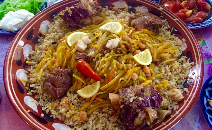 Uzbek plov on traditional plate with yellow carrots-Uzbekistan food