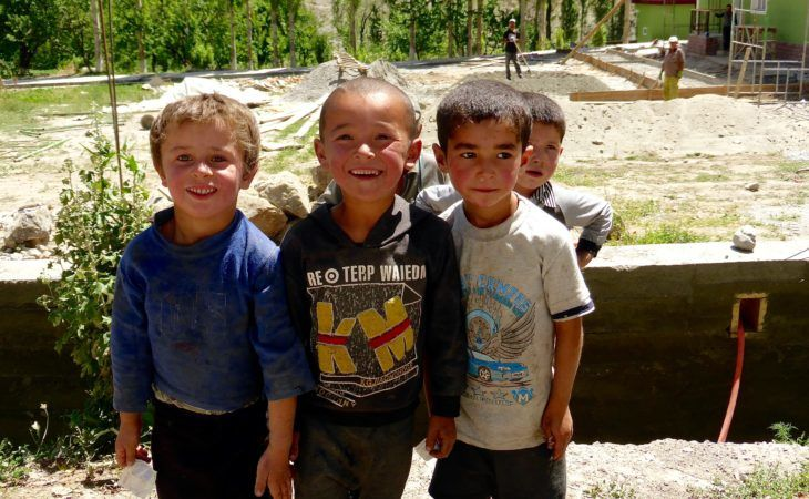 blond kid in the fann mountains of tajikistan-with local dress