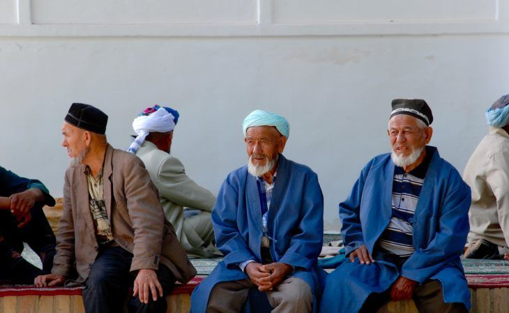Old Uzbek people sitting in front of the mosque in Best of Central Asia tour