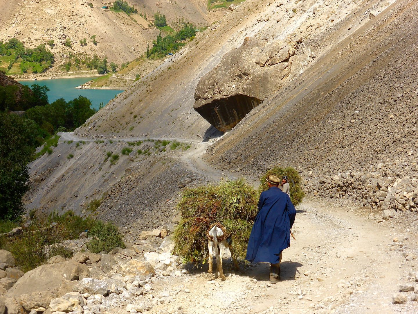Old men walking on the road to Fann mountains during trekking tour in Tajikistan