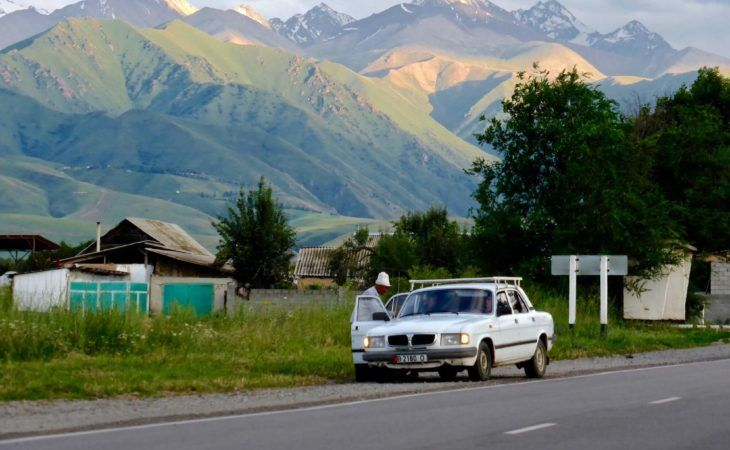 bishkek suburbs with soviet car and man in kalpak hat, Central Asia