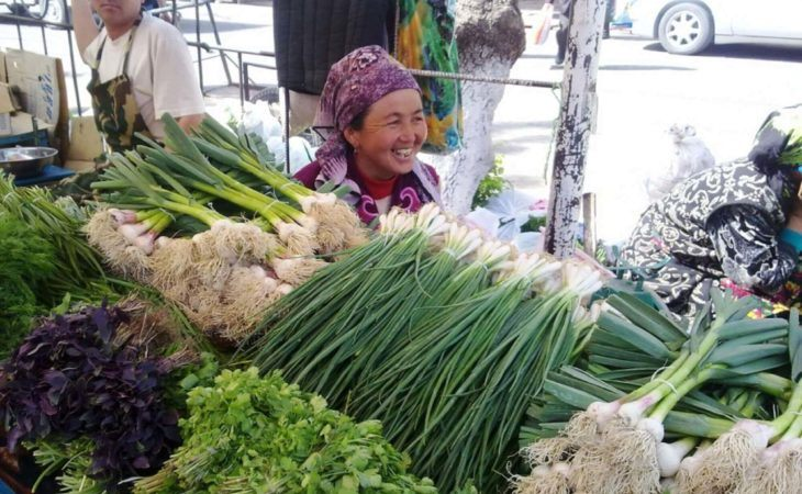 lady selling fresh herbs in bazaar during Kyrgyzstan travel