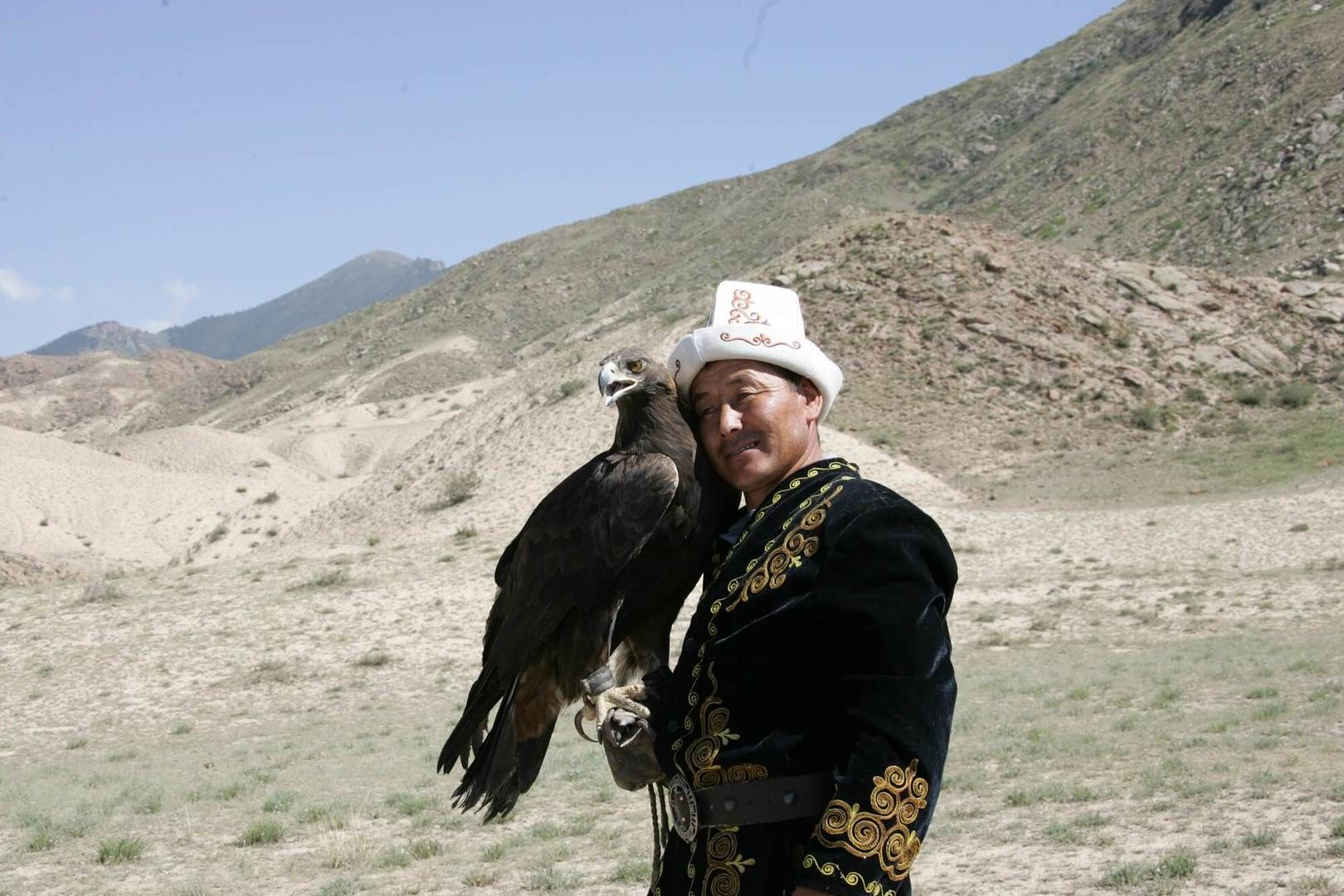 eagle hunter in Kyrgyzstan with Kalpak finds common language with his bird of prey