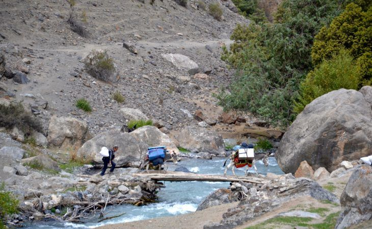 trip to tajikistan involves scenic briidges with local people working in the fields in summer
