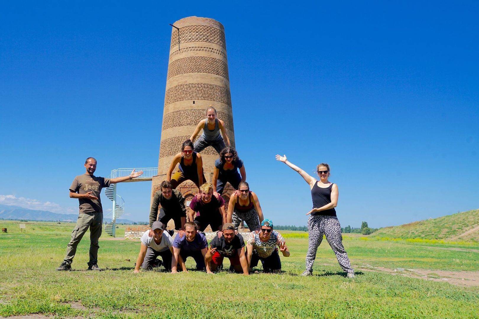 tourist group building a human pyramid in front of the Burana tower