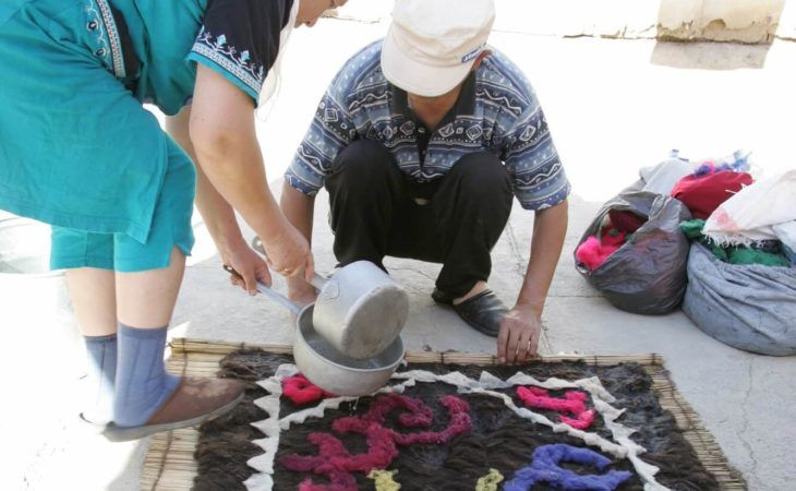 Traditional family making felt carpet Shyrdak in Kyrgyzstan tour