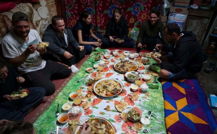 hospitality in kyrgyzstan group tour eating together in a yurt