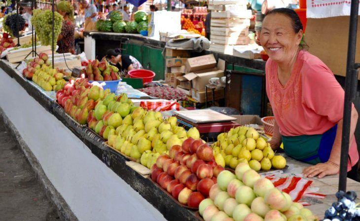 Kyrgyz woman selling fresh goods in osh bazaar in Kyrgyzstan, telling hard pronunciation words