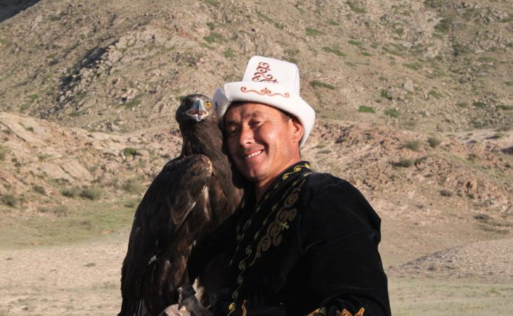 Kyrgyz eagle hunter holding his eagle in Best of Central Asia Tour