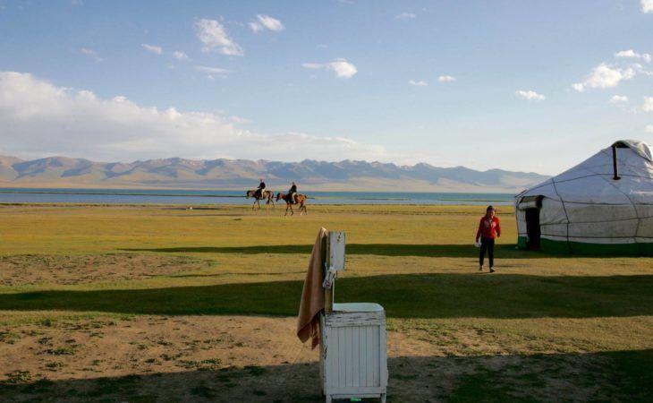 men riding horses near yurt at son kol in Kyrgyzstan & enjoying sunny weather