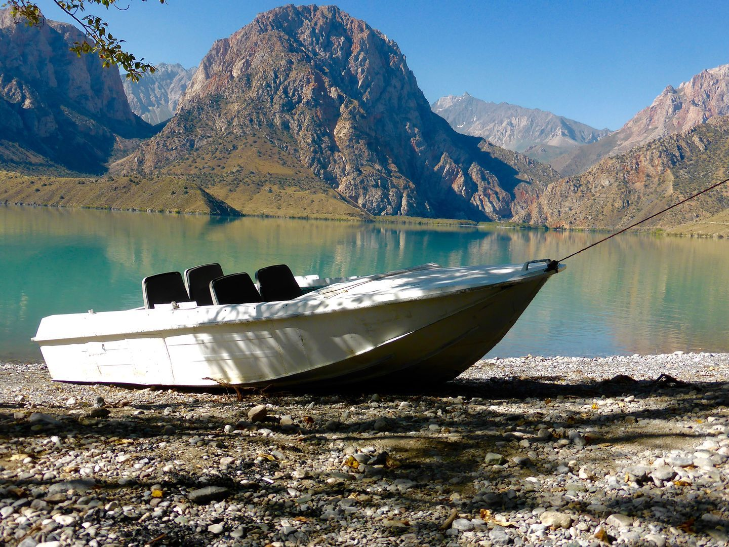 Boat in front of Iskanderkul lake in Best of Central Asia Tour adventure trip