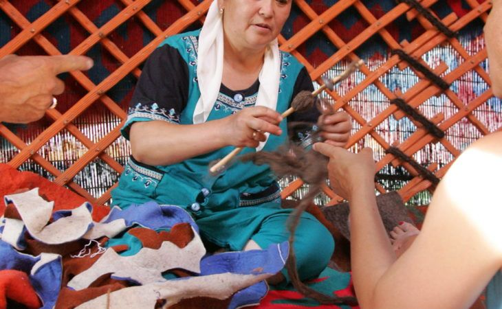 women making traditional felt carpets in yurts of Kyrgyzstan