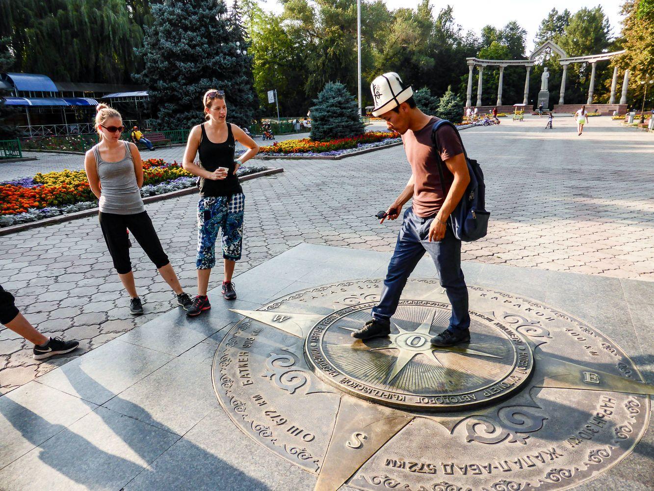 Guide in Kalpak hat telling about Kyrgyzstan in Bishkek city tour