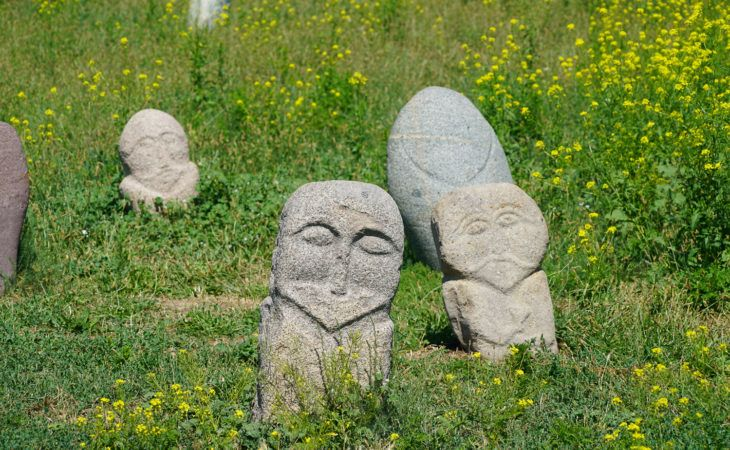 Balbals or anceint stone carvings on grass near burana in Kyrgyzstan trip