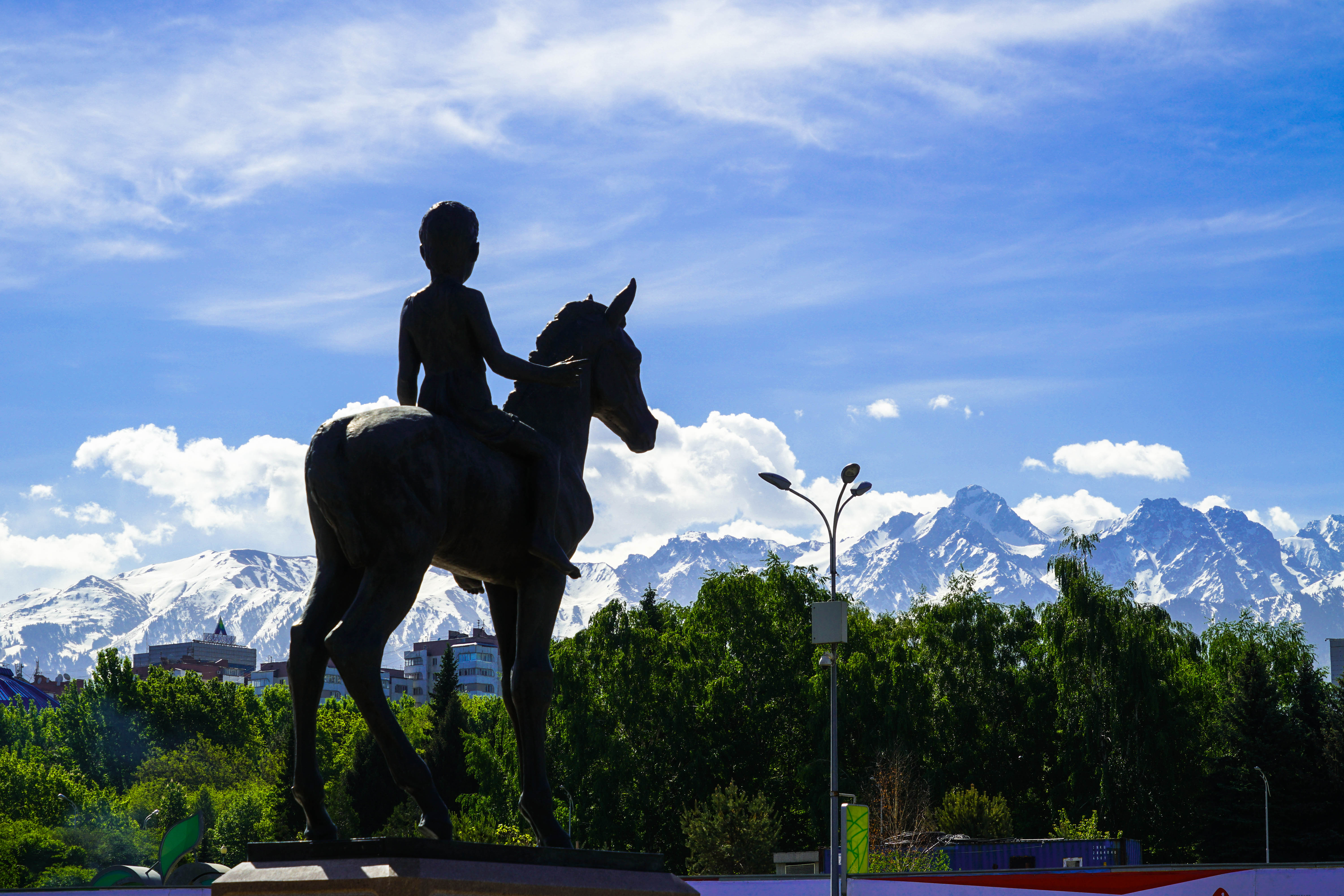 Almaty square horse rider boy with mountain view
